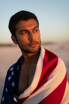 ビーチに立っているアメリカの国旗に包まれた男