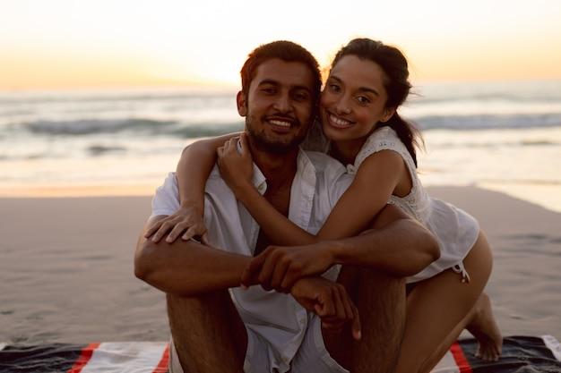 ビーチでお互いを受け入れて若いカップル