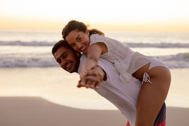 ビーチで女性におんぶを与える男