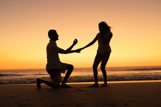 Мужчина предлагает женщину на берегу моря на пляже