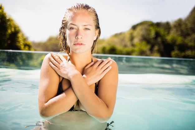 カメラを見てプールで美しいブロンド