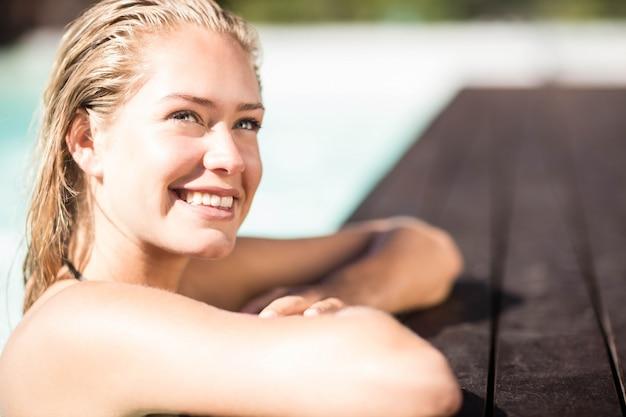 プールの端に寄りかかって見上げる笑顔の金髪