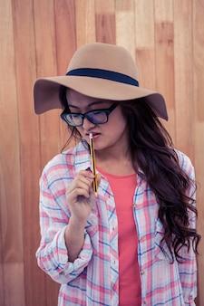 Азиатская женщина в шляпе, держа карандаш на деревянной стене