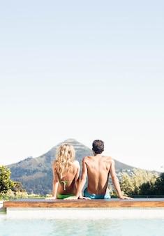 風景を見てプールに座っているカップルの背面図
