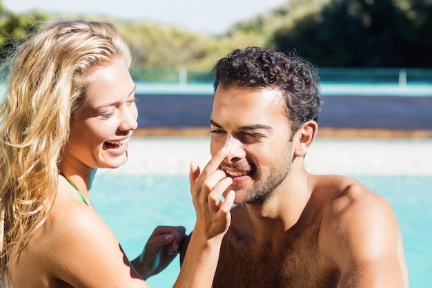 プールでボーイフレンドにクリームを適用するガールフレンド