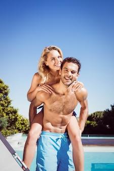 Парень отдаёт поросёнка своей девушке у бассейна