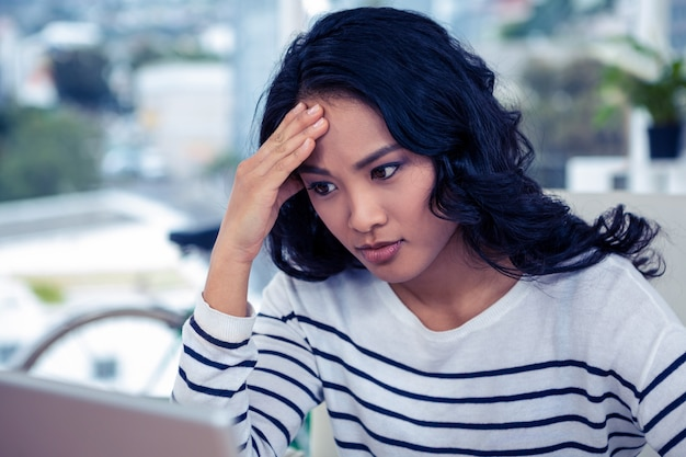 きれいな女性のオフィスで頭の上の手でコンピューターのモニターを見て