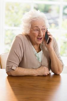 高齢者の女性が自宅で電話をかける