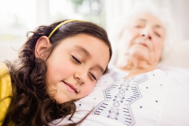 リラックスした孫娘と祖母のソファーで昼寝