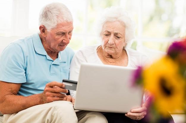 自宅でラップトップを使用して焦点を当てた年配のカップル