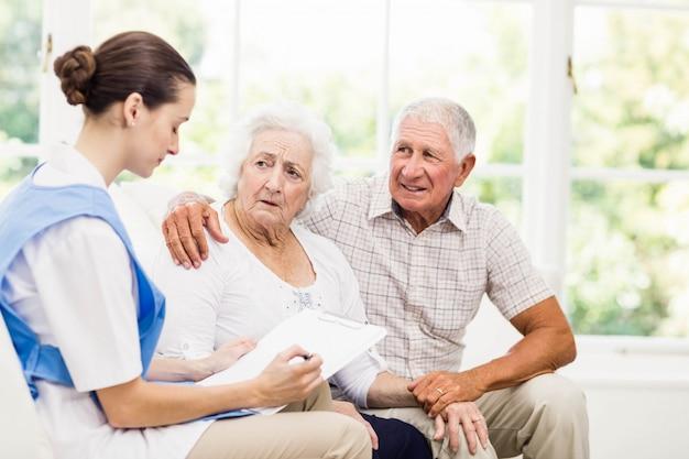 自宅で病気の高齢患者の世話をする看護師