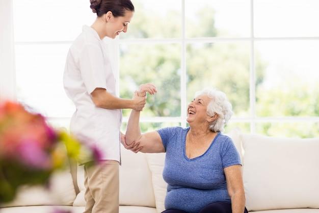 Физиотерапевт ухаживает за больным пожилым пациентом дома