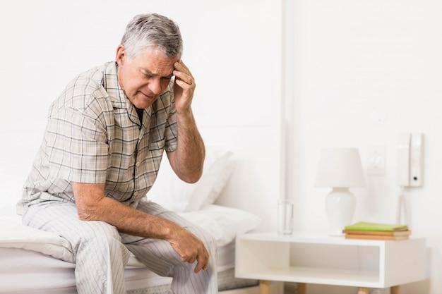 自宅で彼の額に触れる苦しんでいる年配の男性