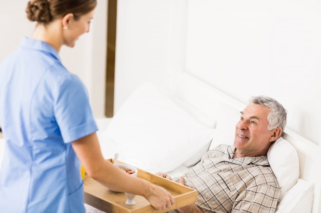 自宅で苦しんでいるシニア患者の世話をする看護師