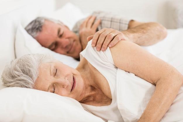 Пожилая пара спит в постели у себя дома