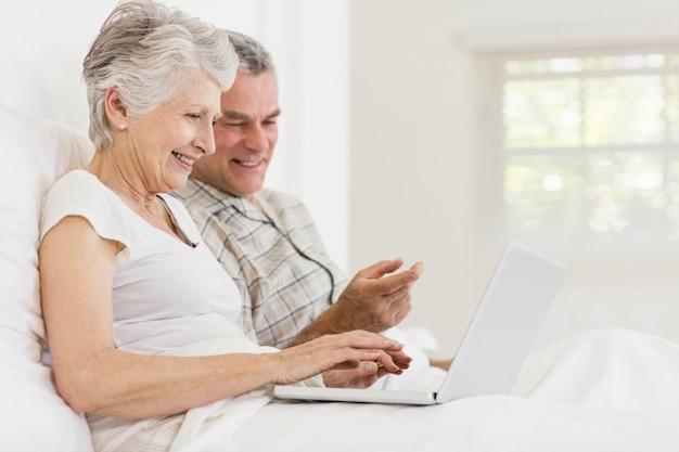 ベッドの上に座ってラップトップを使用して年配のカップル