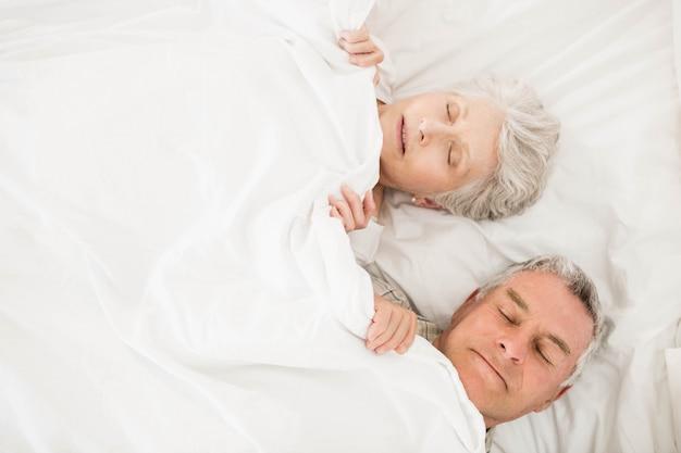 毛布の下のベッドで寝ている年配のカップル
