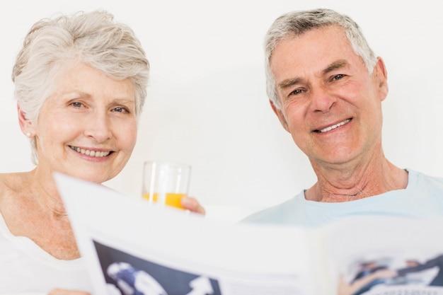ベッドで新聞を読んで年配のカップル