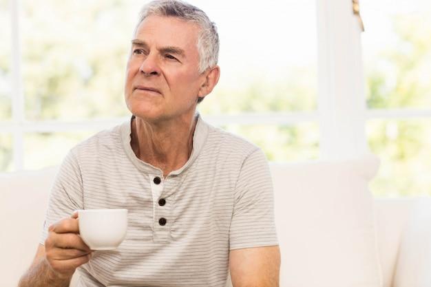 ソファの上にマグカップを保持している思慮深い年配の男性