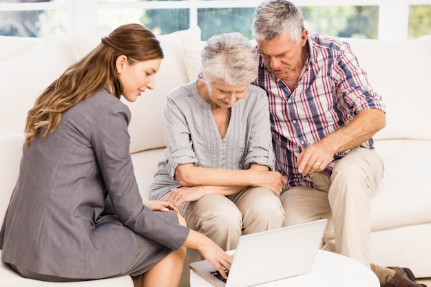 年配のカップルが自宅でラップトップモニターを示す笑顔の実業家