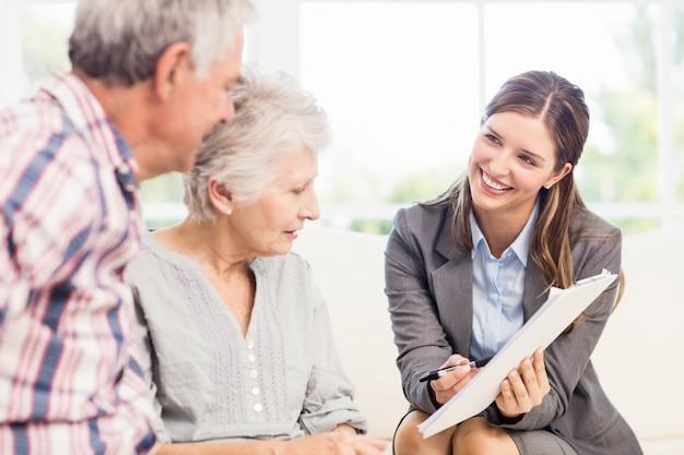 リビングルームで年配のカップルにドキュメントを示す笑みを浮かべて実業家