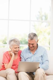 ソファの上のラップトップを使用して笑顔の年配のカップル