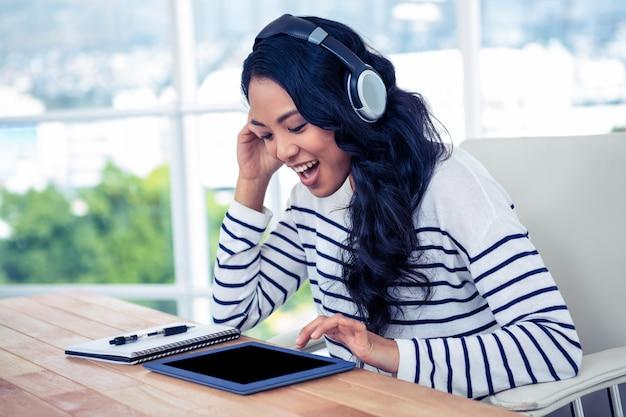 オフィスでタブレットを使用してヘッドフォンで笑顔のアジア女性