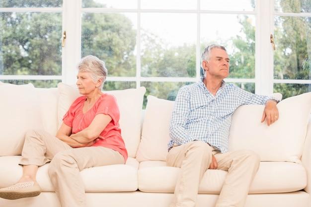 ソファの上の議論の後話していない年配のカップル