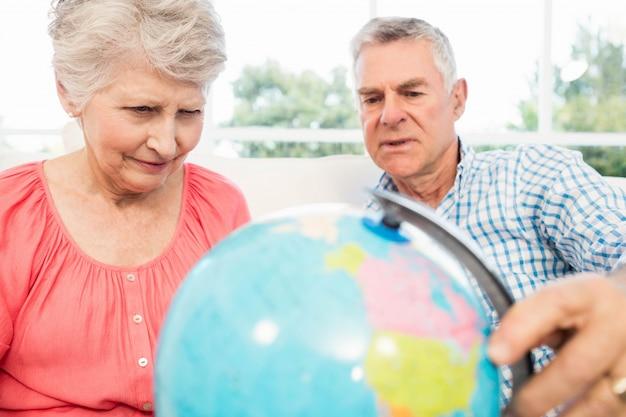 Улыбающиеся старшие пары, глядя на глобус на диване