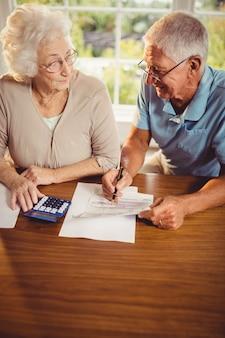 年配のカップルが自宅で手形を数える