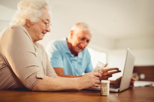 ラップトップを使用して、自宅で薬を保持している年配のカップル
