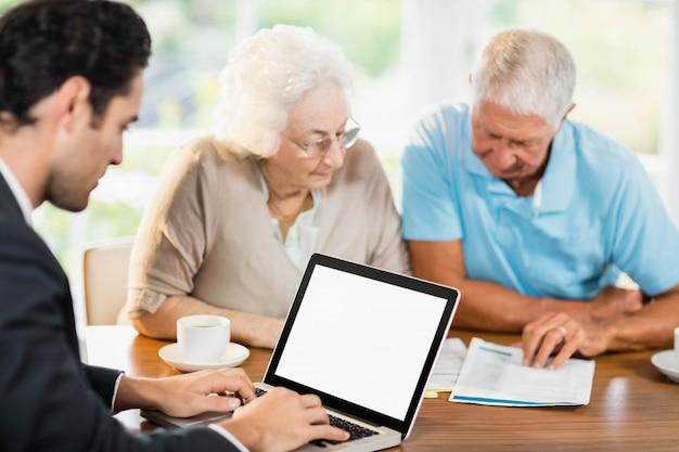 年配のカップルが自宅で文書を読んでいる間にラップトップを使用して実業家
