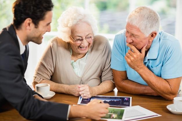 自宅で年配のカップルにシートを示す実業家