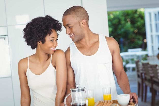 自宅のキッチンで朝食トレイを持って幸せなカップル