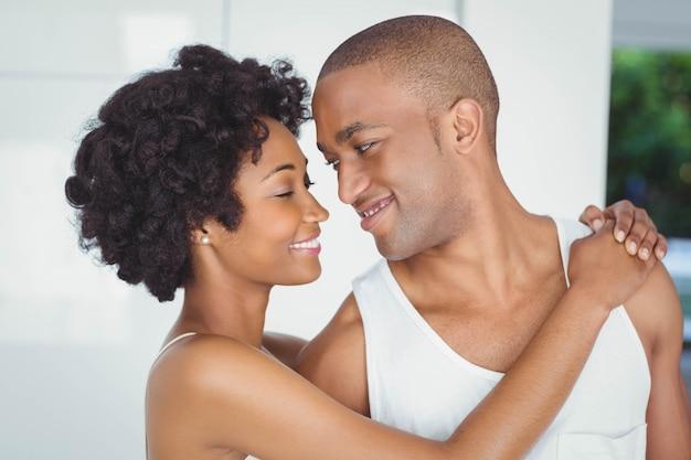 幸せなカップルを抱き締めると、自宅でお互いを見て
