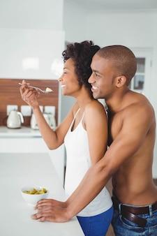 自宅のキッチンで一緒に果物を食べて幸せなカップル