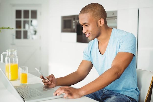 自宅の居間でノートパソコンとスマートフォンを使用して笑みを浮かべて男