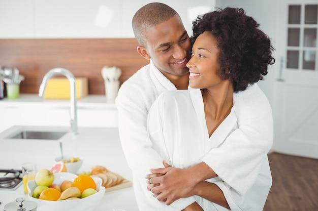 自宅のキッチンで抱いて幸せなカップル