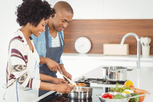 幸せなカップルが一緒に野菜を調理