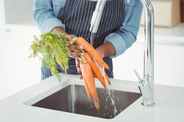台所でニンジンを洗う人の中央部