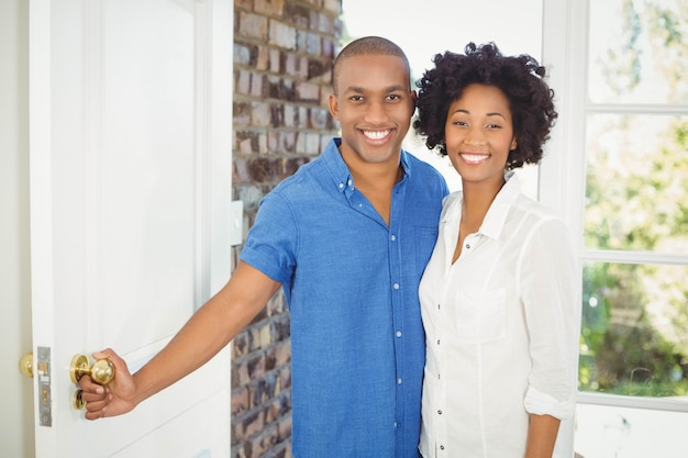 家のドアを開ける幸せなカップル
