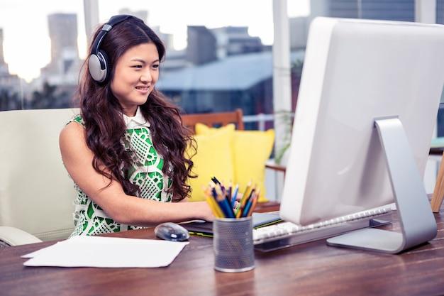 オフィスのコンピューターを使用してヘッドフォンで笑顔のアジア女性