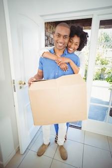 Счастливая пара держит коробку в своем доме