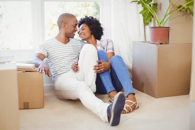 Счастливая пара сидит на полу в гостиной