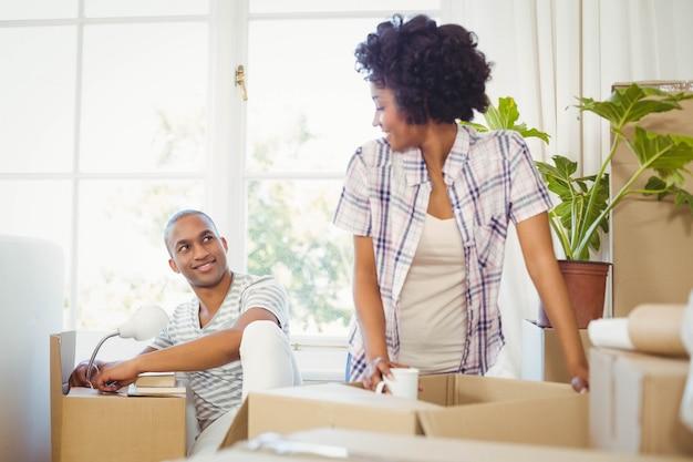 Счастливая пара открывая коробки в гостиной