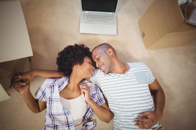 リビングルームの床に横たわって、幸せなカップル