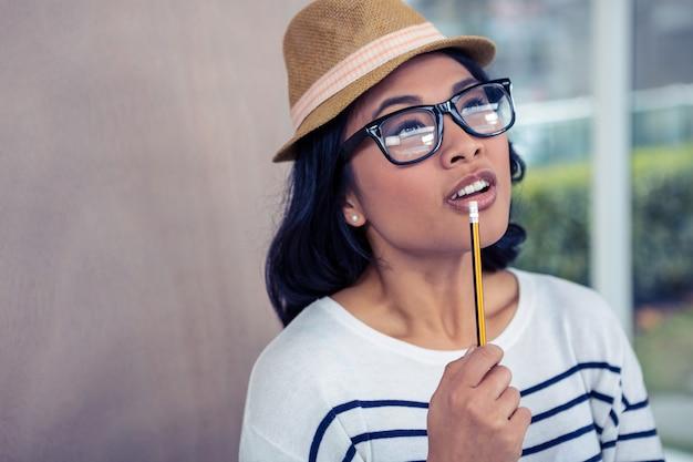 Заботливая азиатская женщина с карандашем на рте стоя в офисе