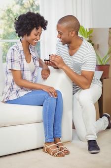 リビングルームで彼のガールフレンドに婚約指輪を提供しているハンサムな男