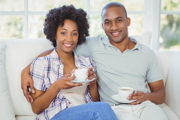 リビングルームでコーヒーを飲みながらソファで幸せなカップル