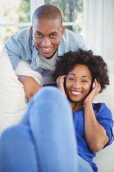自宅のリビングルームでカップルを笑顔の肖像画